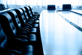 Photo of a long and empty table in a board room